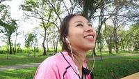 Ung asiatisk kvinna slappnar av sig själv genom att lyssna på musik.