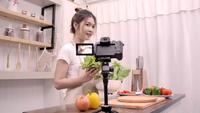 Blogger Asian woman using camera recording how to make salad healthy food video for her subscriber.