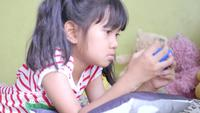 Little girl play video game in living room.
