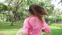 Zeitlupe - junge asiatische Frau, die am Morgen auf Bürgersteig läuft.