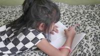 Asiatisk tjej väljer penn och gör läxor i vardagsrummet.