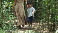 Mamma och son går och leker i skogen