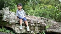 The boy sitting on a rock in nature.