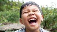 Close up of a laughing boys face after hearing a joke
