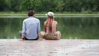 Couple assis au bord du lac assis au bord d'une jetée en bois.