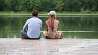 Junte sentarse en el lago que se sienta al borde de un embarcadero de madera.