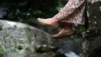 Frau, die ihren Fuß durch den See sitzt am Rand eines hölzernen Docks schwingt