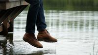 Hombre balanceando su pierna junto al lago sentado en el borde de un muelle de madera