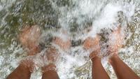 Ciérrese para arriba de pies relajantes en una cascada.