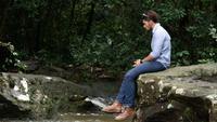 Viajando homem balançando a perna enquanto relaxa pelo riacho.