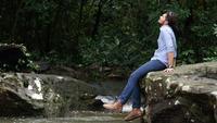 Reisender Mann, der sein Bein bei der Entspannung durch den Nebenfluss schwingt.