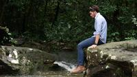 Resande man svänger på benet medan han kopplar av vid bäcken.
