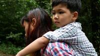 Mor och son piggyback går i naturen.