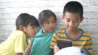 Niños con teléfono inteligente en casa.