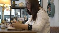 Mulher que usa o telefone esperto e escrevendo notas no restaurante.