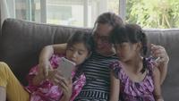 Familia asiática feliz que toma Selfie con Smartphone.