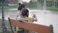 Família asiática feliz que toma Selfie com Smartphone.
