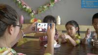 Família asiática feliz comendo sorvete e tomando selfie com smartphone.