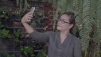 Frau, die selfie mit Smartphone nimmt.
