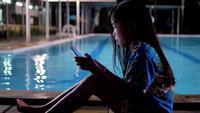 Muchacha asiática de los niños que usa el teléfono elegante que se relaja cerca de piscina.