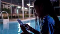 Menina asiática das crianças que usa o telefone esperto que relaxa perto da piscina.
