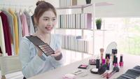Beautiful asian woman reviewing makeup