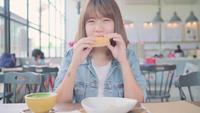 Asiatin, die Brot isst und Kaffee beim Sitzen auf einer Tabelle in einem Café trinkt.