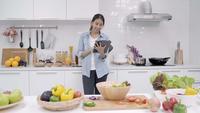 Heureuse femme asiatique à l'aide d'une tablette pour la recette tout en préparant un repas dans la cuisine.