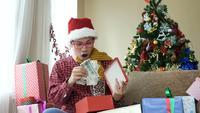 Stilig ung man öppnar sin julklapp