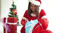 Mujer vestida como la señora Claus preparando una bolsa de regalo para navidad.