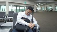Vermoeide zakenmanslaap terwijl het wachten op het vliegtuig bij luchthaven.