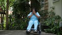 Disabled senior woman sitting on a wheelchair in a hospital park