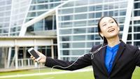 Empresaria escuchando música y bailando fuera de la oficina