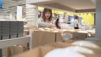 De jonge Aziatische vrouw berijdt boodschappenwagentje die nieuw meubilair in pakhuis kiezen.