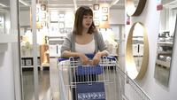 Young Asian woman rides shopping cart choosing new furniture in warehouse.