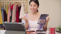 Happy beautiful young Asian woman use cosmetics review make up tutorial broadcast live video to social network.