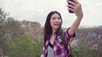 Blogger Asian backpacker kvinna spelar in vlog-video på toppen av berget.