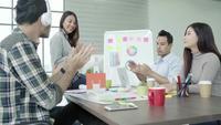 Grupp av tillfälligt klädda affärsmän diskuterar idéer på kontoret.