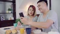 Attractive young Asian couple distracted at table with newspaper and cell phone while eating breakfast.