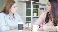 Las mujeres de negocios asiáticas que disfrutan de beber café caliente, discuten sobre el trabajo.