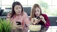 Asian women using smartphone and eating popcorn in living room at home.