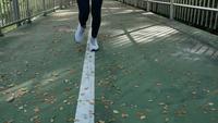 Ung asiatisk kvinna som går på trottoaren på morgonen.