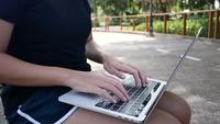 Beautiful asian young woman sitting at bench in park using laptop.