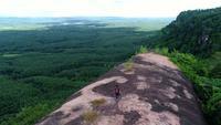 Fotógrafo caminando por el borde de un acantilado por encima de las montañas
