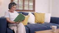 Asian elderly woman reading a book in the living room at home.