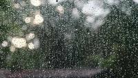 Närbild på ett fönster med regndroppar som faller ner