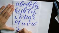 Woman hand writes a calligraphic alphabet