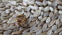 Anéis de casamento acessório deitado sobre uma mesa de palha