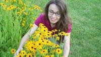 Mujer joven que huele flores amarillas
