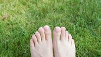 Kvinnans fötter på gräset